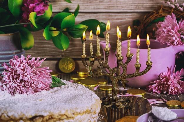 Żydowska menora ze świecami i świątecznym ciastem ozdobiona kwiatami