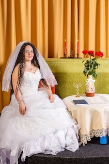 Żydowska panna młoda w białej sukni ślubnej z welonem siedzi przy stole z kwiatami przed chupą.