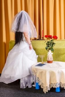 Żydowska panna młoda w białej sukni, z zawoalowaną twarzą, stoi plecami przed ceremonią chupa.