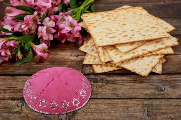 Żydowski chleb matzah z jarmułką i kwiatami na drewnianym