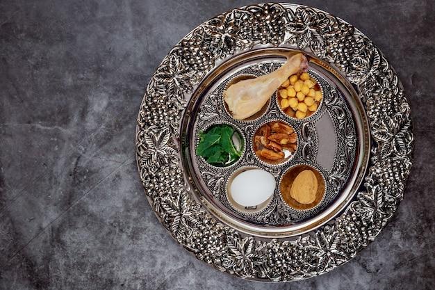 Żydowski seder z jajkiem, kością, ziołami i orzechami. koncepcja święta paschy.