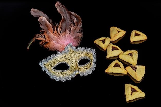 Żydowskie ciasteczka hamantaschen i maska karnawałowa na święto purim.