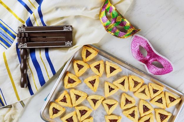 Żydowskie ciasteczka hamantaschen na blasze z maską na purim.