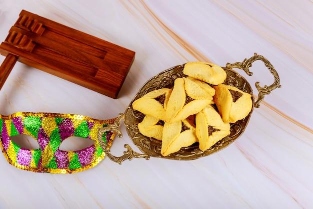 Żydowskie karnawałowe święto purim na ciasteczkach hamantaschen, noisemaker i masce z pergaminem