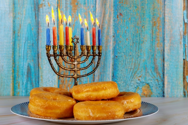 Żydowskie święto chanuka pączki i menora ze palącymi się świecami na talerzu