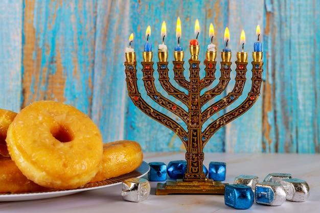 Żydowskie święto chanuka z menorą, pączkami i dreidelami