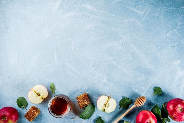 Żydowskie święto rosz haszana lub koncepcja święta jabłka, z czerwonymi jabłkami, liśćmi jabłka i miodem w słoiku, jasnoniebieski stół powyżej