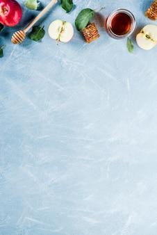 Żydowskie święto rosz haszana lub koncepcja święta jabłka, z czerwonymi jabłkami, liśćmi jabłka i miodem w słoiku, jasnoniebieskie tło powyżej