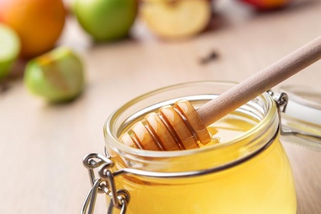 Żydowskie święto rosz haszana z miodem i jabłkami na drewnianym stole.