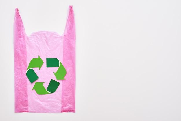 Żyj na zielono. symbol na białym tle recyklingu w różowej plastikowej torbie. ponowne użycie znaku redukcji recyklingu. gospodarka odpadami i recykling