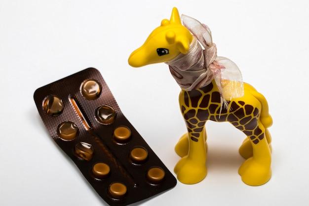 Żyrafa z taśmą na szyi w pobliżu leków na białym tle