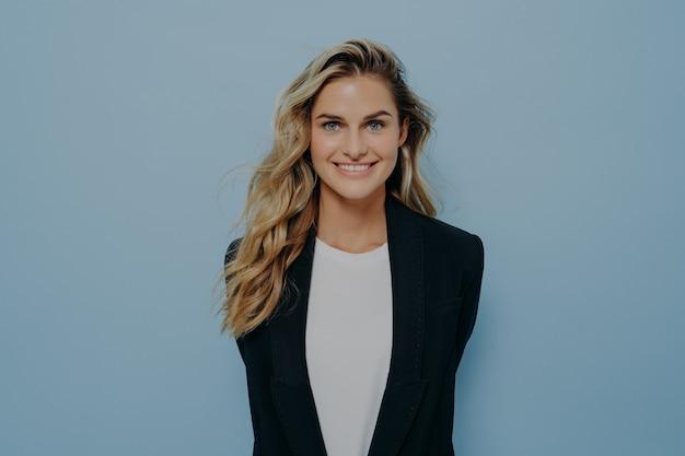 Żywa młoda blond kobieta w czarnej stylowej marynarce ze szczęśliwym, promiennym uśmiechem, stojąca z rękami za plecami, jakby ukrywała niespodziankę, na białym tle na niebieskim tle studia