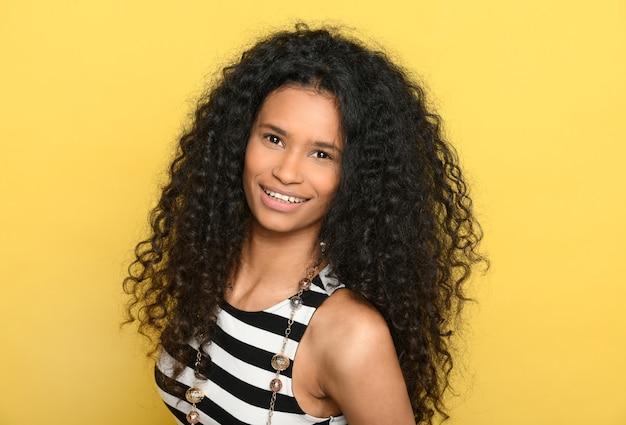 Żywa, szczęśliwa, przyjazna młoda czarna kobieta z uroczym uśmiechem na wspaniałych grubych kręconych długich włosach na portrecie głowy i ramion