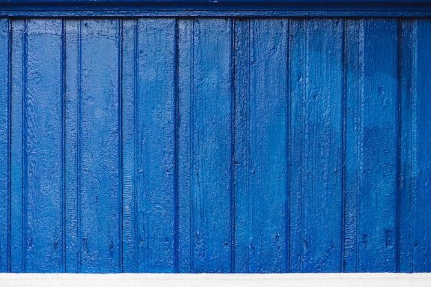 Żywe drewniane deski z bliska. gruba kobaltowa farba na nierównych płytach. niedoskonała drewniana tekstura zewnętrznej części wiejskiego domu. świeżo malowane drewniane panele na ścianie domu.