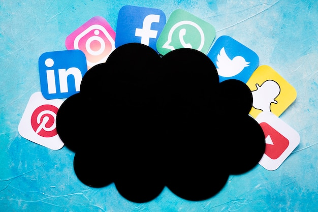 Żywe ikony aplikacji telefonu komórkowego rozmieszczone wokół chmury czarnego papieru