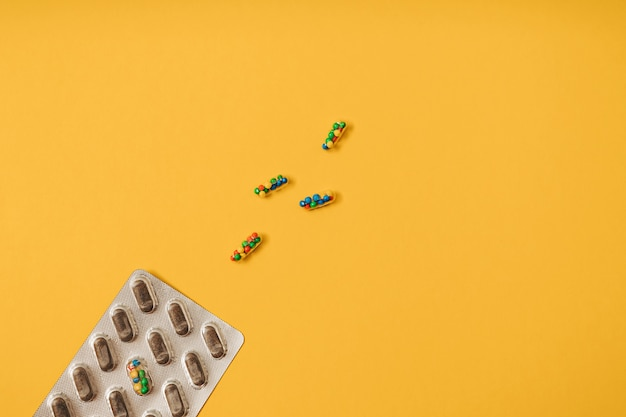 Żywe kolorowe płaskie ułożenie kapsułek pigułek lekarskich wypełnionych cukierkami cukrowymi kropi na żółtym tle. kreatywna koncepcja przedawkowania leków i uzależnienia od suplementów diety.