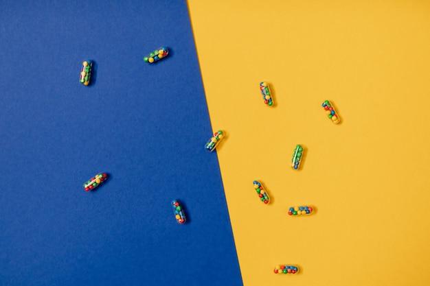 Żywe kolorowe płaskie ułożenie kapsułek pigułek lekarskich wypełnionych cukierkami cukrowymi posypuje się na żółtym i niebieskim tle. kreatywna koncepcja przedawkowania leków i uzależnienia od suplementów diety.
