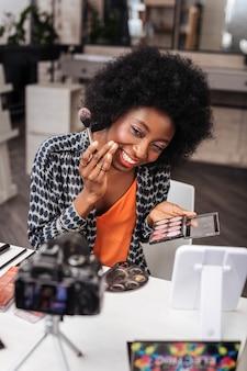 Żywe kolory. ładna ciemnoskóra kobieta z koralową szminką robi makijaż podczas prowadzenia samouczka online