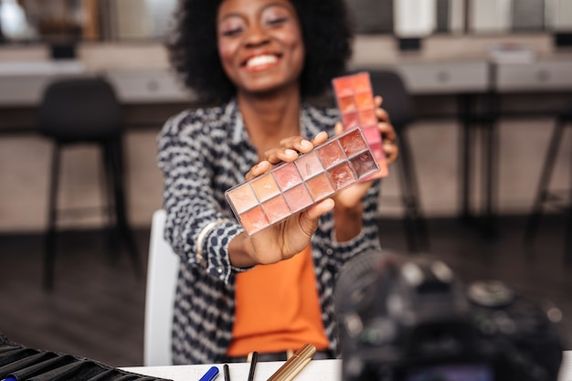 Żywe kolory. piękna ciemnoskóra modelka z kręconymi włosami uśmiecha się, demonstrując nową paletę kolorów