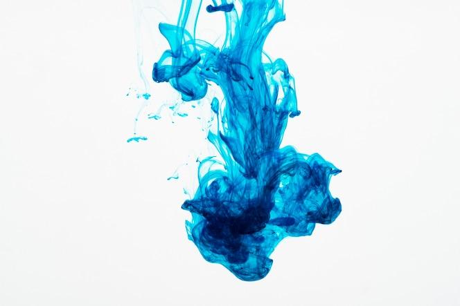 Żywe niebieskie kropelki atramentu pod wodą
