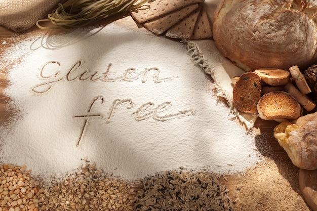 Żywność bezglutenowa. różne makarony, chleb i przekąski na drewnianym