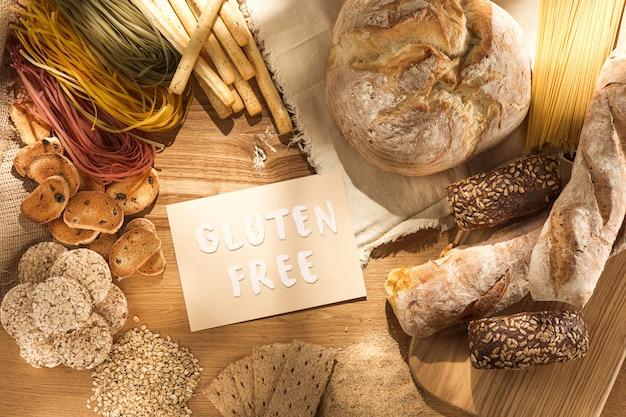 Żywność bezglutenowa. różne makarony, chleb i przekąski na podłoże drewniane z widoku z góry