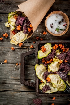 Żywność dietetyczna. dieta wegańska. suszone warzywa. domowe frytki z buraków, marchwi i cukinii. na starym drewnianym stole w stylu rustykalnym, ze świeżymi warzywami. widok z góry lato