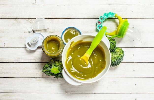 Żywność dla niemowląt puree dla dzieci z brokułów na białym tle drewnianych