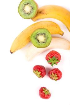 Żywność ekologiczna, zdrowa żywność, kiwi, truskawka i bananakiwi, truskawka i banan na białej powierzchni