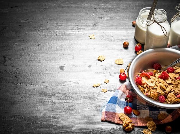 Żywność fitness. musli z dojrzałymi jagodami i mlekiem na czarnym drewnianym stole.