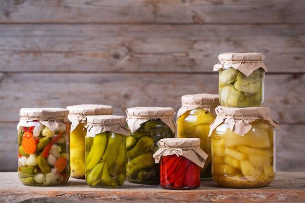 Żywność konserwowana i fermentowana. asortyment domowych słoików z różnymi marynowanymi i marynowanymi warzywami na drewnianym stole. gospodarstwo domowe, ekonomika domu, konserwacja zbiorów
