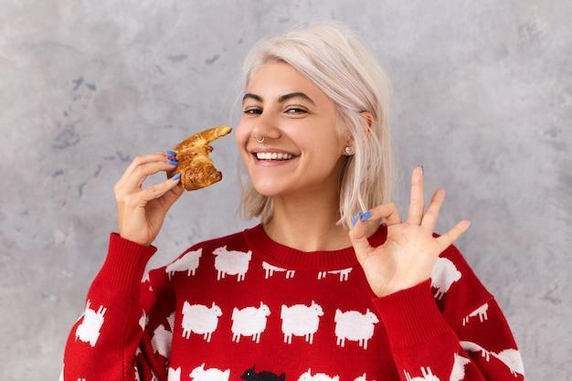 Żywność, piekarnia i ciasta. śliczna nastolatka trzymająca czekoladowy rogalik przestrzegająca ścisłej diety, pomagająca sobie słodkim deserem bez wyrzutów sumienia, nie bojąca się przybrać na wadze, pokazująca ok gest