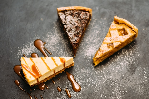 Żywność piekarnicza. asortyment deserów. tarta orzechowa, szarlotka i posypana cukrem pudrem.