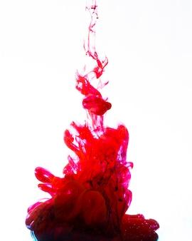 Żywy czerwony atrament wirujący pod wodą