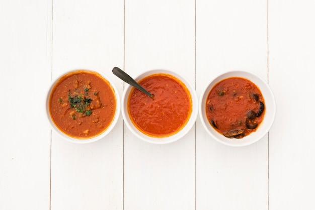 Żywy czerwony sos miska ułożone w rzędzie na drewnianym stole biały