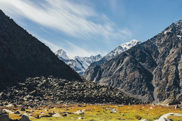 Żywy jesienny krajobraz z góralską doliną w słońcu i ośnieżonymi górami pod błękitnym niebem z chmurami cirrus. kolorowa górska sceneria z nasłonecznioną doliną w jesiennych barwach i ośnieżonymi górami.