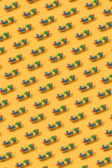 Żywy kolorowy wzór kapsułek pigułek lekarskich wypełnionych cukierkami cukrowymi kropi na żółtym tle. kreatywna koncepcja przedawkowania leków i uzależnienia od suplementów diety. transparent.