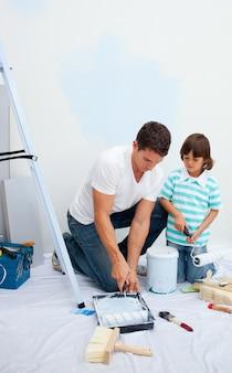 Żywy ojciec i jego syn malują w nowym domu