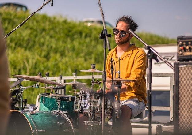 Żywy perkusista w okularach przeciwsłonecznych gra na swojej perkusji