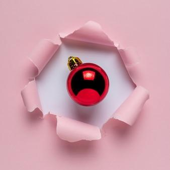 Żywy różowy zgrywanie papieru z czerwoną bombką