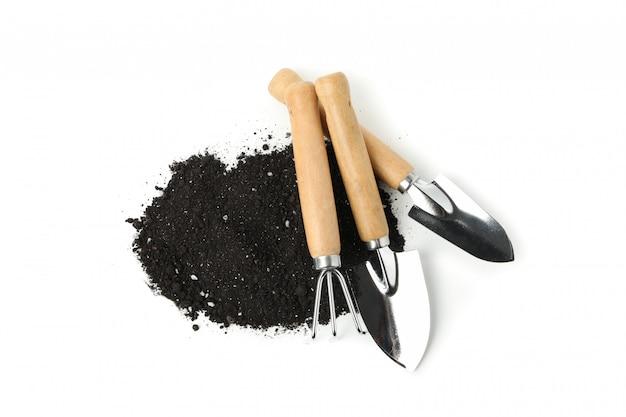 Żyzne gleby i narzędzia ogrodnicze na białym tle