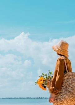 Zza młodej kobiety odpoczywającej na plaży dziewczyna w słomkowym kapeluszu ciesząca się pięknym widokiem zdjęcia z tyłu