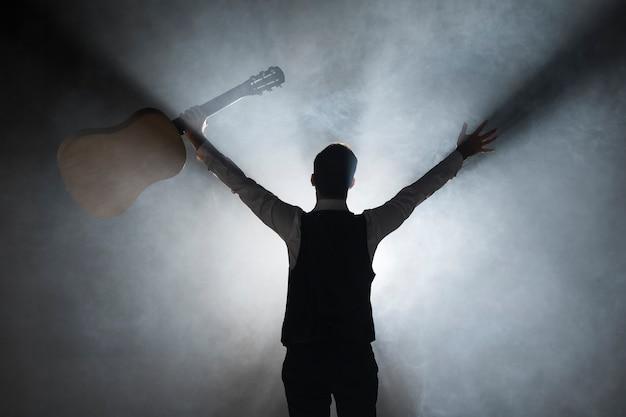 Zza strzału muzyk trzymający gitarę na scenie