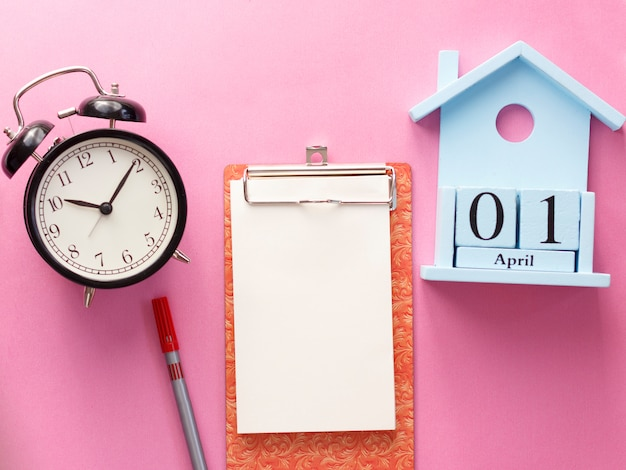 1 de abril calendario de madera del día del tonto, cuaderno, reloj, pluma. aplanado sobre fondo rosa.