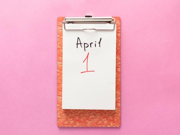 1 de abril día del tonto, cuaderno. aplanado sobre fondo rosa.