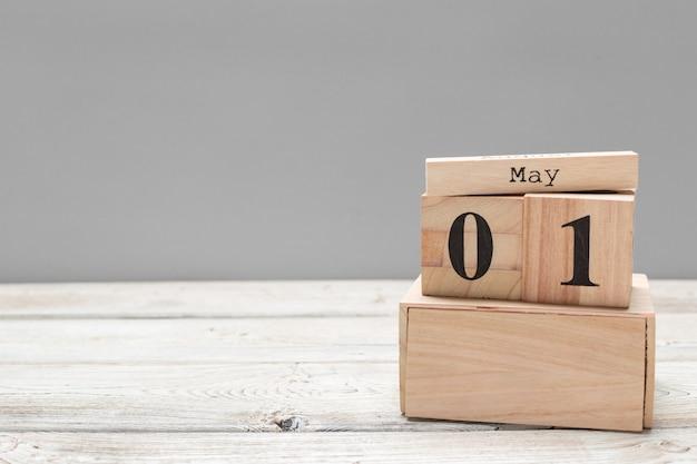1 de mayo. imagen del 1 de mayo calendario de color madera en mesa de madera. día de primavera, espacio vacío para el texto. día internacional de los trabajadores