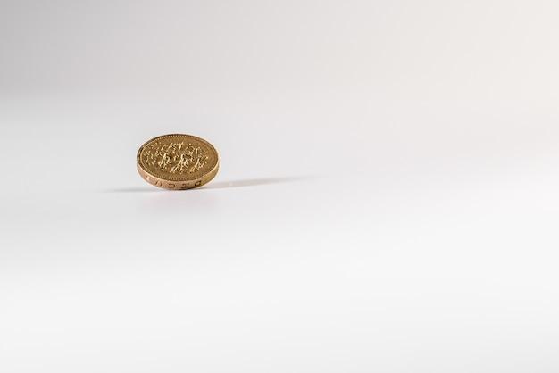 1 moneda de libra británica cayendo sobre fondo blanco, aislado