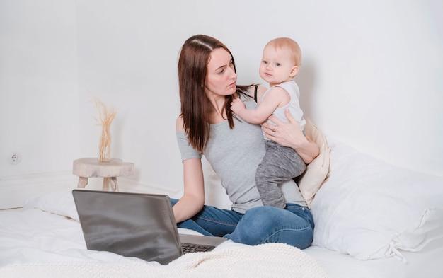 1 mujer blanca joven sentada en una cama con un niño pequeño y trabajando en una computadora portátil, madre joven que trabaja en casa