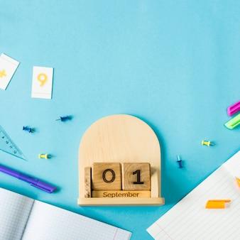 1 de septiembre en un calendario de madera entre los suministros para el estudio sobre un fondo azul.
