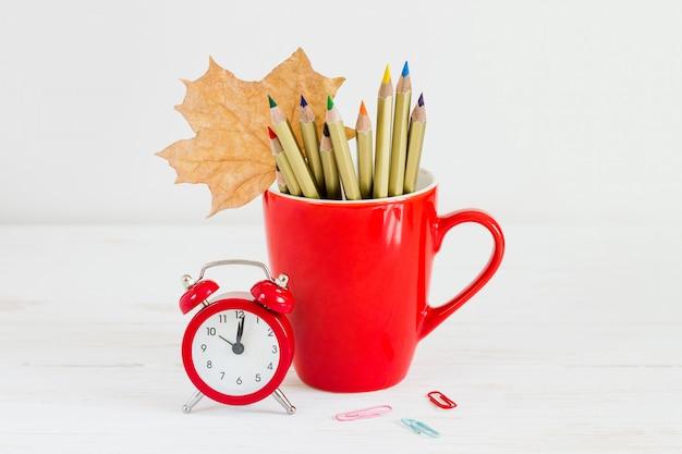 1 de septiembre de concepto. despertador rojo, taza, lápices de colores y hoja de arce. concepto de regreso a la escuela